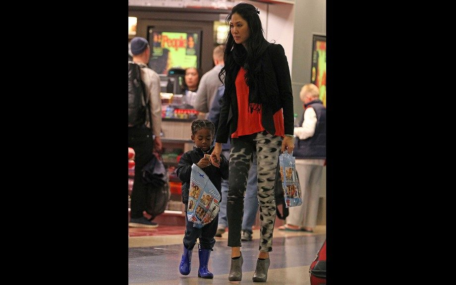 Kimora Lee Simmons while boarding a flight at LAX with son Kenzo, is cute and casual in a red top, black jacket, and gray booties, and Brand Glacier Printed Skinny Jeans. Photo Credit: Splash