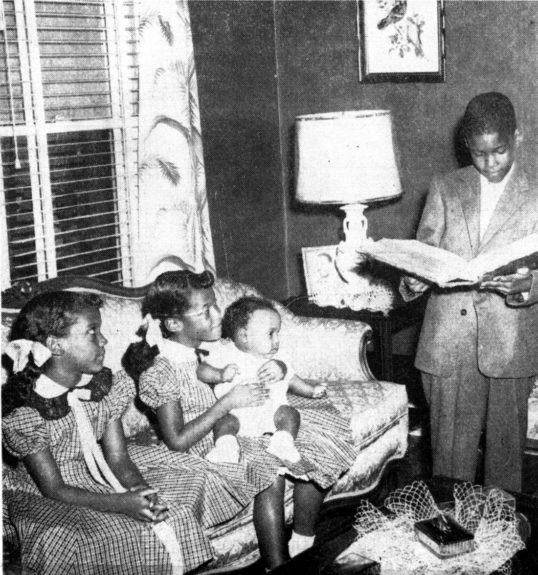 Dr. Boyd reading with sisters, 1957