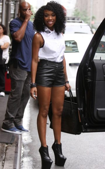 Brandy wears a white blouse, black leather shorts, and Giuseppe Zanotti wedge booties. Photo Credit: Splash