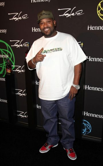 Bun B rocks a Supreme fitted, Bape t-shirt, jeans, and red & gray sneakers. Photo Credit: Getty