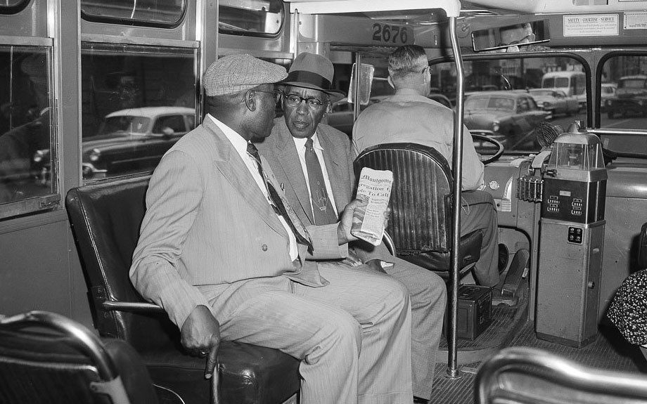 Two men sit in the first seat behind the driver of a city bus in Montgomery, Alabama after the U.S. Supreme Court ruled racial segregation on the city buses unconstitutional.