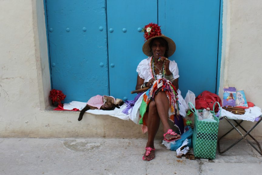 Older Cuban woman posts up in Old Havana, charging tourists for pictures.