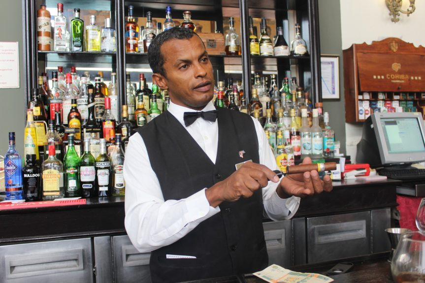 Cuban bartender at the Hotel Nacional teaches Lifers how to cut and light a cigar.