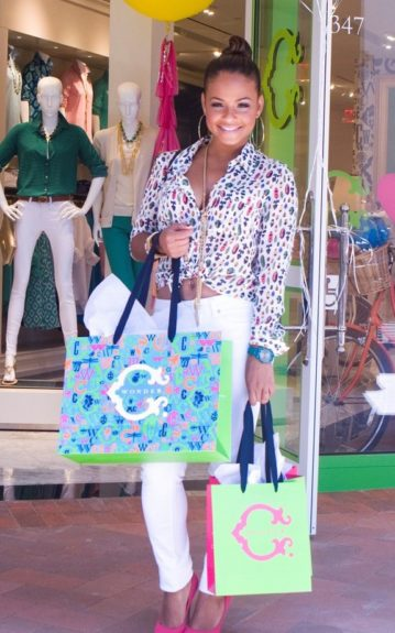 Christina Milian wears a printed silk blouse, white skinny jeans, and pink pumps as she shops. Photo Credit: INF