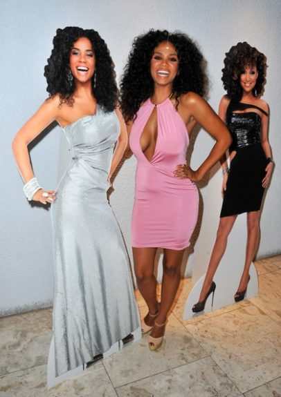 """Claudette Ortiz has us seeing double at the """"R&B Divas LA"""" premiere as she poses next to her lifesize photo while rocking a pink keyhole dress and nude pumps. <em>photo: WENN</em>"""