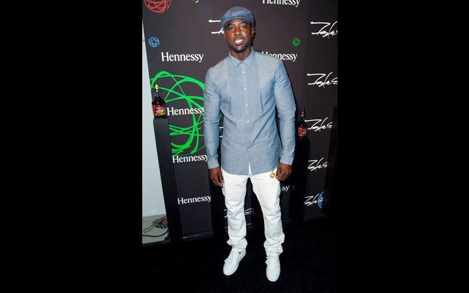 Lance wears a blue button down, white jeans, and white sneakers, with a blue paperboy cap. Photo Credit: Getty