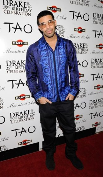 Drake has been showing mad love to Versace lately and hit up nightclub Tao in a royal blue Versace button down, black pant, black boots and shades. <em>Photo</em>: Splash