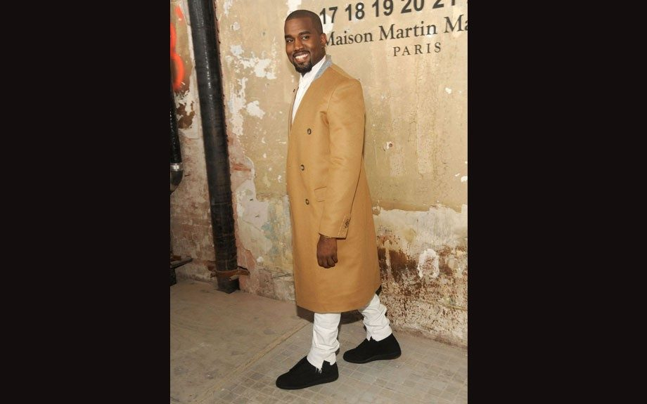 Kanye West attends H&M's Maison Martin Margiela kickoff last night in a brown trench coat from the forthcoming brand.