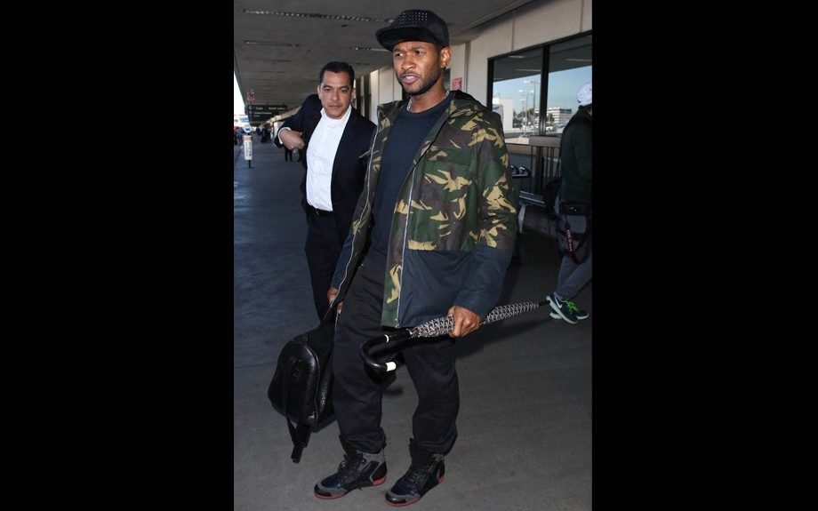 Usher was spotted at LAX, in a Hentsch Man Camouflage and Navy Jacket, Stampd LA studded hat, Lanvin snakeskin embossed sneakers, and a Goyard umbrella. Photo Credit: Splash