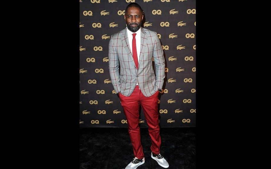 Idris Elba has been known to raise a heart rate and things were no different at the GQ Men of the Year Awards in Paris. He sported a red and grey check blazer, red pants, and Christian Louboutin Golfito wing-tip shoes. Photo Credit: Getty