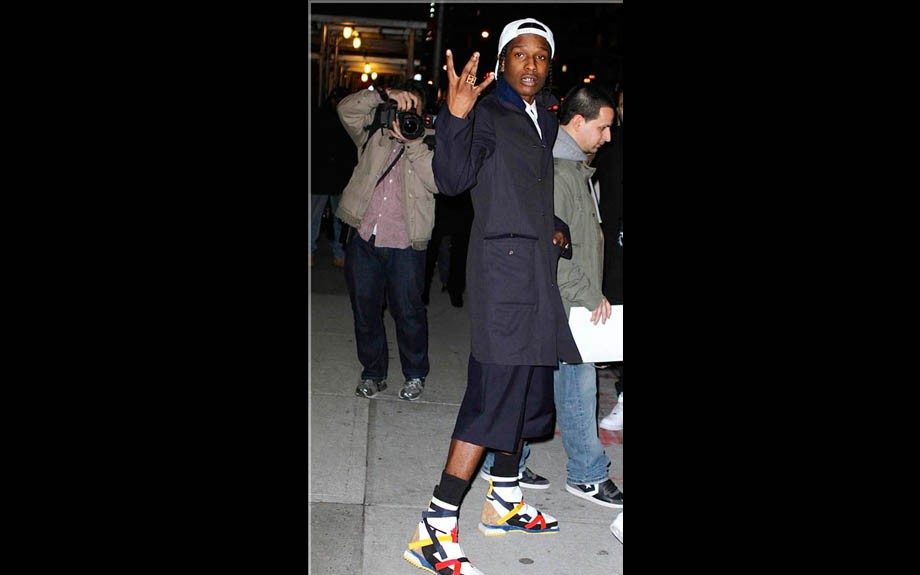 Rapper A$AP Rocky exits the David Letterman show in an all navy outfit anchored by a pair of Raf Simons De Stijl Lego Multicolored printed boots…done so well! Photo Credit: Getty