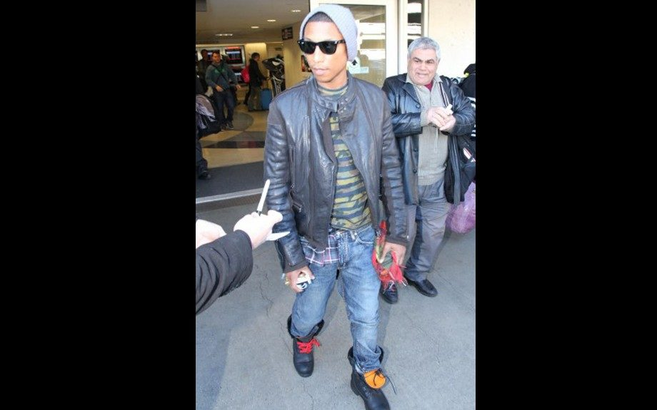 Pharrell Williams went grunge as he was seen exiting LAX Airport in a very expensive Lanvin motorcycle jacket, striped graphic tee, and a plaid shirt underneath. Photo Credit: Splash