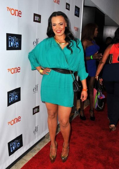 Faith poses in teal dress, black leather waist belt, strappy black purse, gold jewelry, and multicolored pumps…we aren't loving it but we're always loving her. <em>photo: WENN</em>