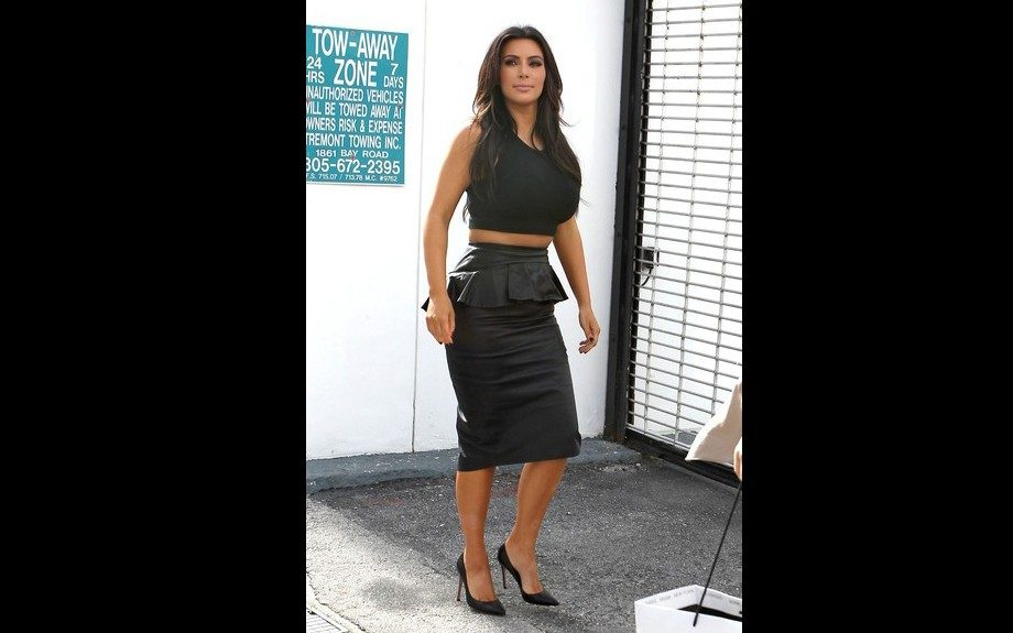 Kim Kardashian in Miami in all black top and Alexander McQueen Leather Peplum Skirt. Photo Credit: Splash
