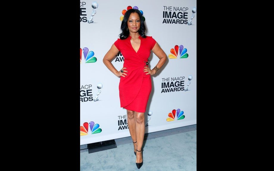 Garcelle Beauvais is beautiful in red wearing a wrap around dress, and black pumps. Photo Credit: Getty