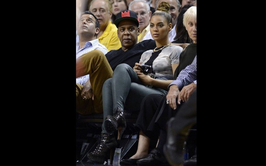"Jay-Z attended the Miami Heat vs. Atlanta Hawks game with wifey Bey donning a black v-neck and khakis, accented by Air Jordan 1 ""Brooklyn Zoo"" sneakers and a $100 IamRonBass BassQuiat SnapCap. Photo Credit: INF"