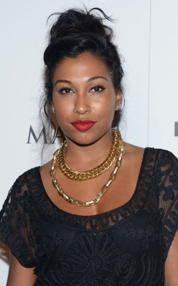 Melanie Fiona goes for Goth in an embroidered black top, gold heavy metal jewelry and a matte red lip