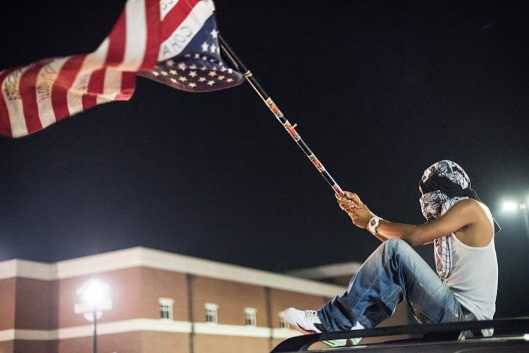 "A protestor outside the Ferguson Police Department holding the ""distressed"" United States flag that was a fixure during the weekend's activities.   	Photo Credit: Aaron Banks"