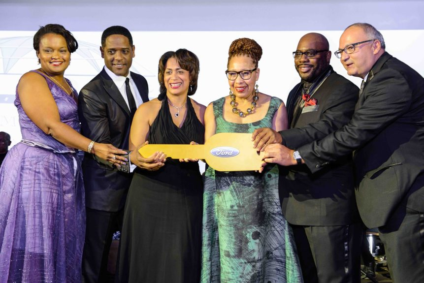 <p> Co-Chair and Museum Trustee Pamela Alexander and Ford Motor Company with Blair Underwood present the key to a new Ford Transit to Wright Museum President & CEO Juanita Moore.</p>