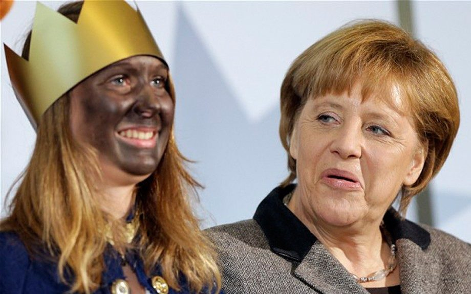 """German Chancellor Angela Merkel wears black face and sings with """"blacked-up"""" children"""