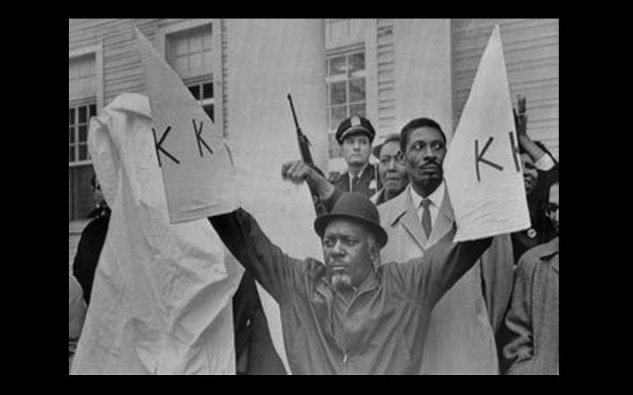 Charles Sims of the Deacons for Defense and Justice in Bogalusa stands defiantly on courthouse steps holding Klan hoods.