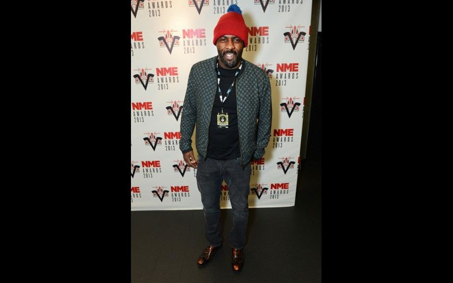 Idris Elba hung out across the pond, in London in his Dolce & Gabanna bomber jacket, and red pom pom hat at the 2013 NME Awards. Photo Credit: Getty