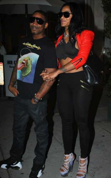 Joseline wears a red cropped jacket, black cropped top, black leggings, and Versace sandals. Stevie J wears a graphic t-shirt, jeans, and black and white sneakers