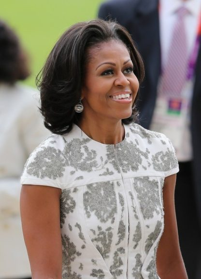Michelle's ensemble consisted of a 2013 collection piece from J.Mendel (white crepe jacket with silver embroidery), a J.Mendel ivory pleated skirt, and pointed toe pumps. Photo Credit: Splash