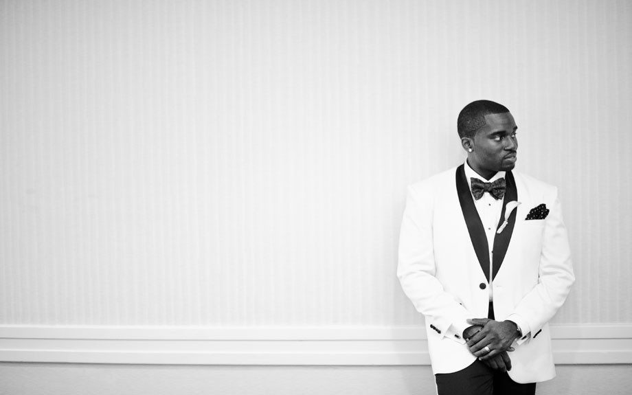 The groom Edward Osefo is dapper in a white tuxedo jacket with black detail. We're loving the bow tie!
