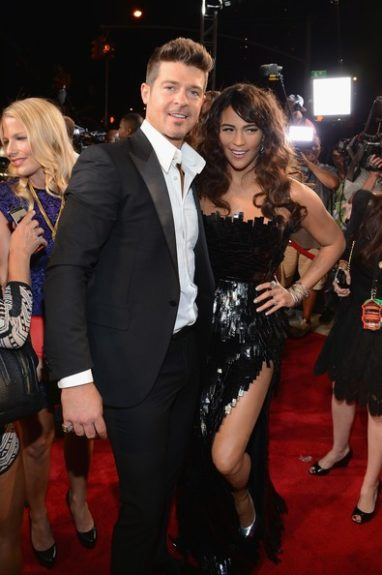 Paula Patton shows a little leg in her sexy shimmery black Lever couture gown, as she posed with her suave hubby Robin Thicke. Photo Credit: Getty
