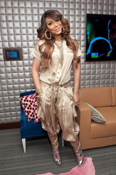 """Promoting her album on <em>106 & Park</em> back when Tamar wasn't ready to share her little """"love on top"""" with the world, she masked her bump in this Matthew Williamson flight suit (with a drawstring waistline), golden accessories, and silver Giuseppe Zanotti heels."""