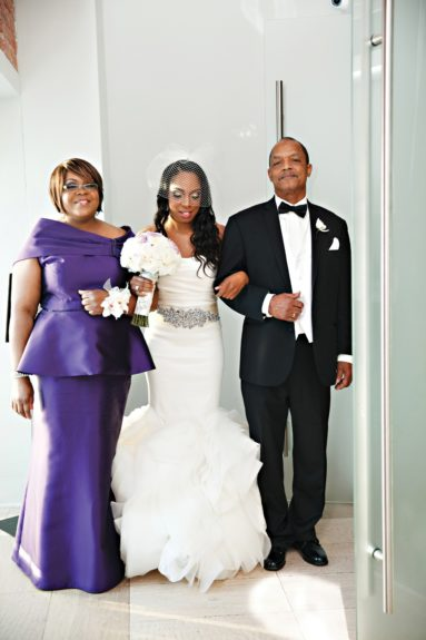 The bride is escorted to her groom by her parents.
