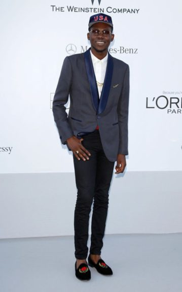 Theophilus London rocks his cool signature style with a dapper twist in a blue USA cap to match his blue blazer, black skinny jeans and embroidered loafers