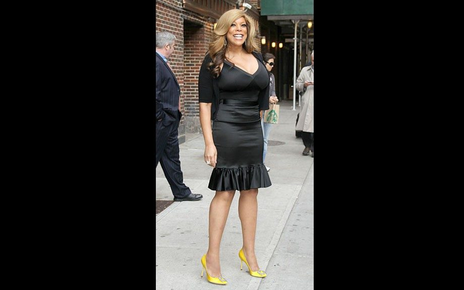 Satin is a tricky material to get right for women with curves, but it looks like Wendy Williams may have pulled it off hiking her satin ruffle skirt waist-high and pairing it with a black bandage top and a black cardigan. The yellow pumps add an awesome pop of color. Well done, Wendy!