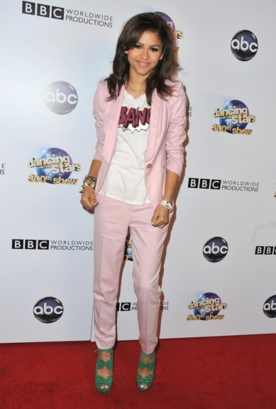 """Zendaya Coleman was on hand at the <em>Dancing With the Stars</em>300th Episode Red Carpet Event in a pink suit, """"Bang"""" graphic tee and a pair of Charlotte Olympia Eve Leaf Booties. Photo Credit: Getty"""