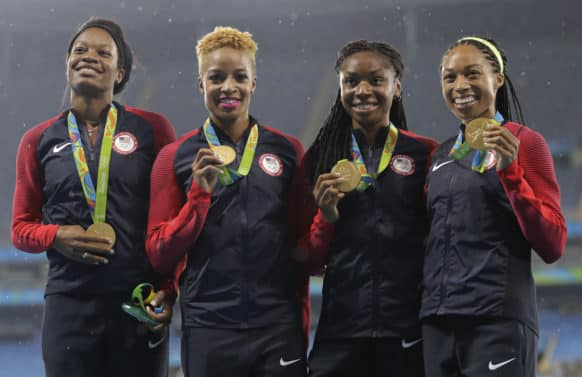 The United States women's 4x400 meter relay team members, Courtney Okolo, Natasha Hastings, Phyllis Francis and Allyson Felix celebrate their gold medals on the podium during athletics competitions at the Summer Olympics inside Olympic stadium in Rio de Janeiro, Brazil, Saturday, Aug. 20, 2016. (AP Photo/Jae C. Hong)