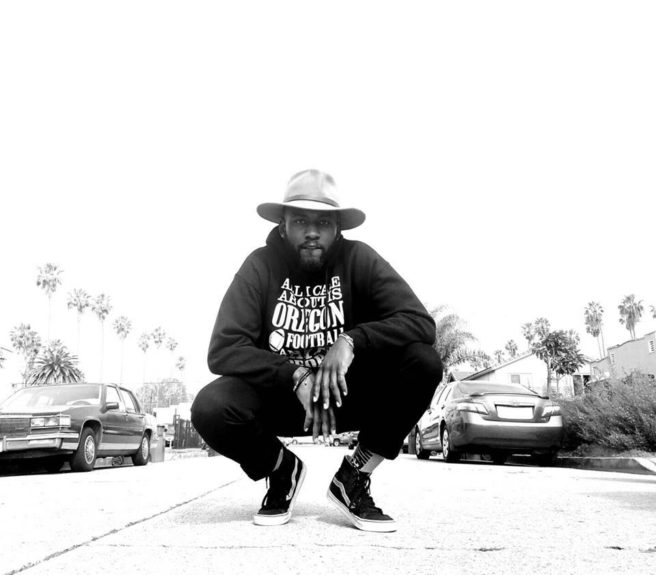 Rapper Buggsy Capri squats on the block he grew up on, flanked by the popular South Central backdrop of palm trees.