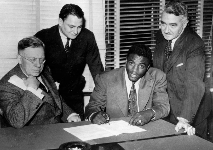Jackie Robinson, first Negro player in the major leagues, signs with the Montreal Royals in Montreal October 23, 1945.  From left are: Royals president Hector Racine, Branch Rickey Jr., Robinson and Royals vice-president Romeo Gauvreau. (AP Photo)