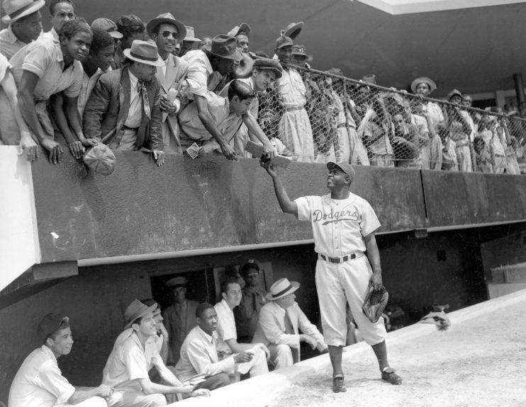 Jackie Robinson, first baseman of the Brooklyn Dodgers, returns an autograph book to a fan in the stands, during the Dodgers' spring training in Ciudad Trujillo, now Santo Domingo, in the Dominican Republic, on March 6, 1948. (AP Photo)