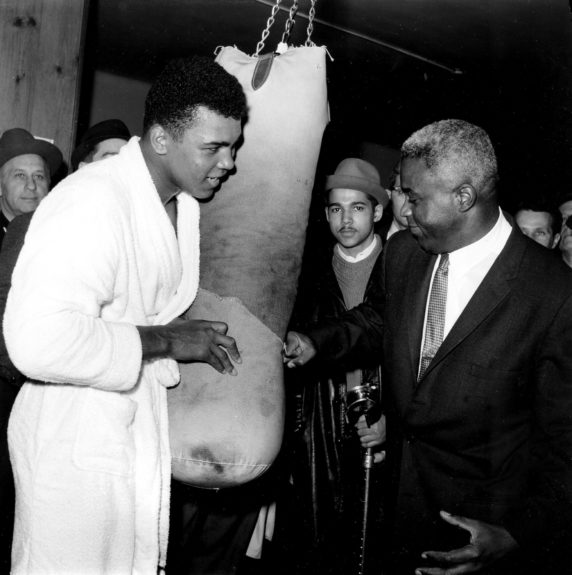 Jackie Robinson, former Brooklyn Dodgers baseball player, hits a punching bag held by heavyweight boxing champion Cassius Clay in a New York gym during his visit on March 13, 1963.  (AP Photo)