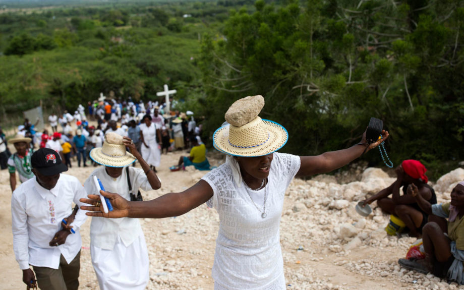 A woman stretches out her arms in prayer as she balances a stone on her head as a form of penance during a Good Friday ritual, in Ganthier, Haiti. April 14. AP / Dieu Nalio Chery