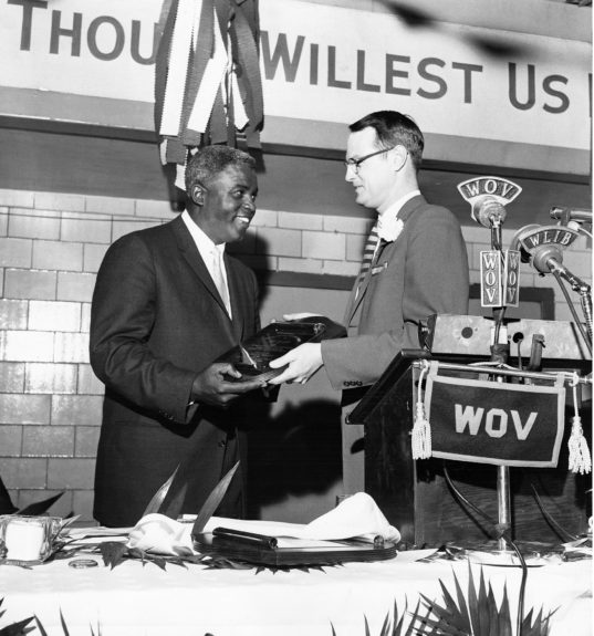 Jackie Robinson is pictured receiving an award from James Tuppeny at the March 1958 Century Club Harlem YMCA Benefit. (Moneta Sleet, Jr./ EBONY Collection)