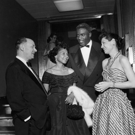 Attending a benefit supper dance for Wiltwyck School boys in the Empire State Building observatory, Jackie Robinson and wife Rachel are pictured chatting with William Keary and Mrs. Louis G. Gowan. (G. Marshall Wilson/ EBONY Collection)