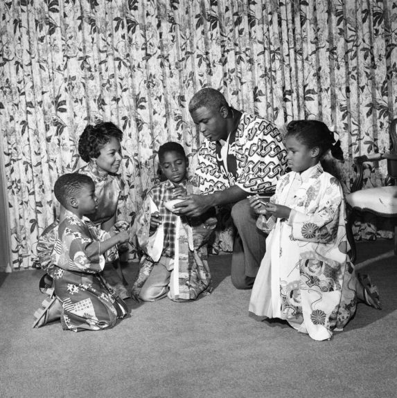 Baseball giant Jackie Robinson, is pictured spending some one-on-one time with his three children and wife in their home. (G. Marshall Wilson/ EBONY Collection)