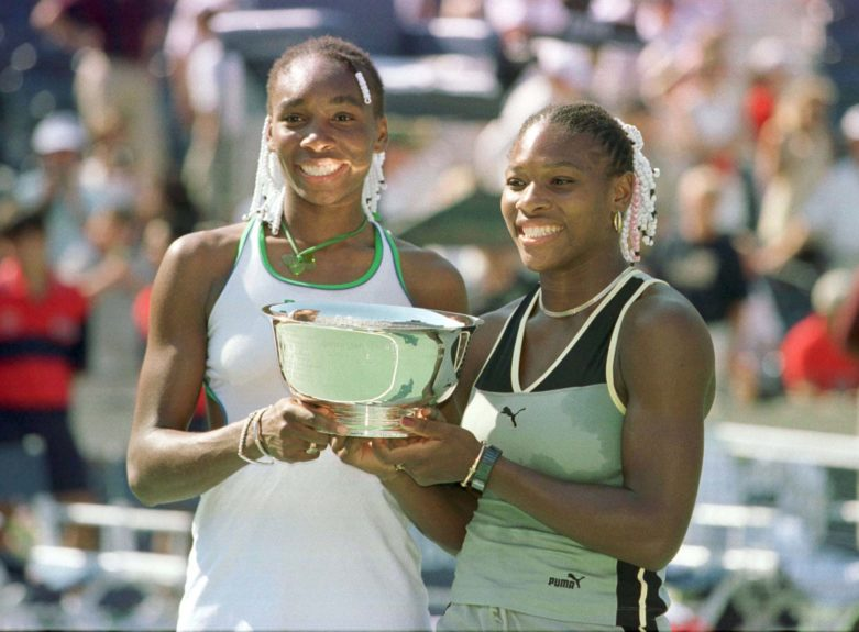 Venus, left, and Serena Williams hold the winners trophy after defeating Sandrine Testud and Chanda Rubin in the doubles final during the US Open on September 12, 1999.