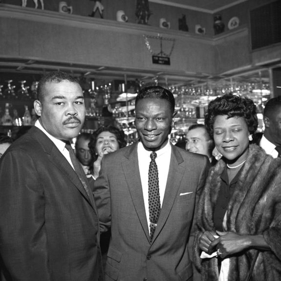 Jazz great Nat King Cole stops for a photograph with American heavyweight champ Joe Louis and wife Rose Morgan Louis.