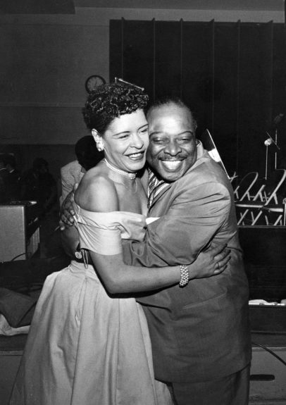 Billie Holliday and Count Basie embrace during performance.