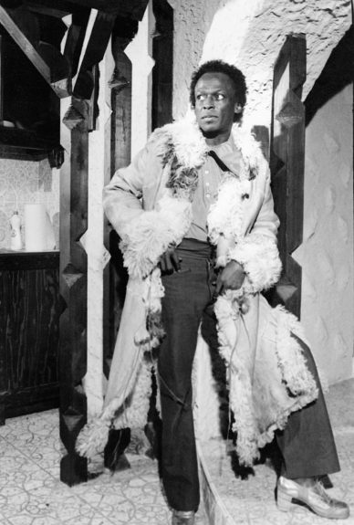 Jazz trumpeter and orchestra leader, Miles Davis models one of his full length coats, this one lined in fur, 1971.