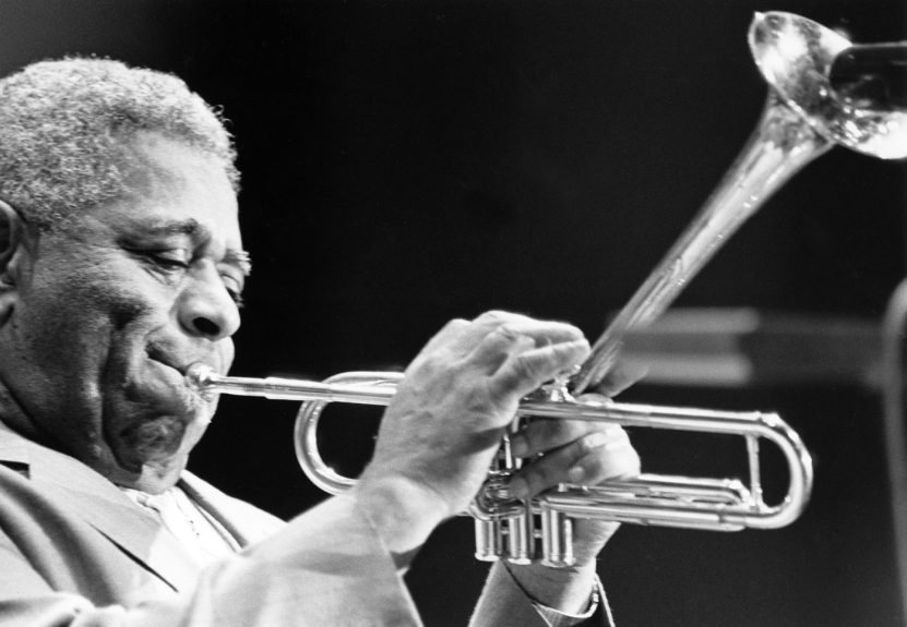 Dizzy Gillespie is eagerly photographed sharing the new special mutes from Sweden he received for Christmas.